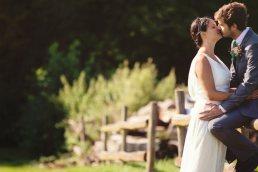 groom on fence kissing bride