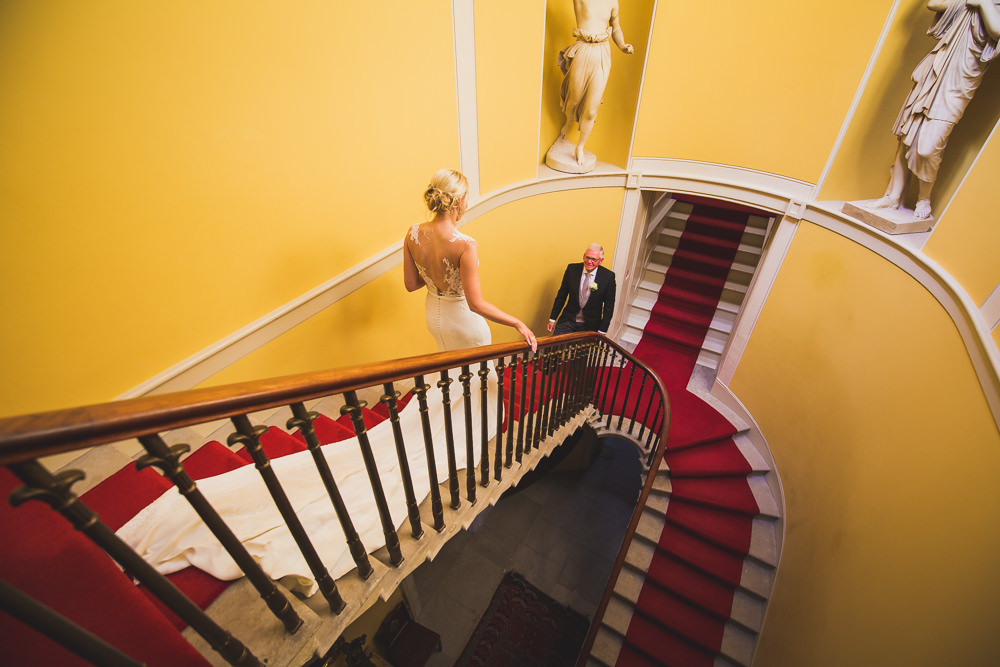bride walking down stairs to father