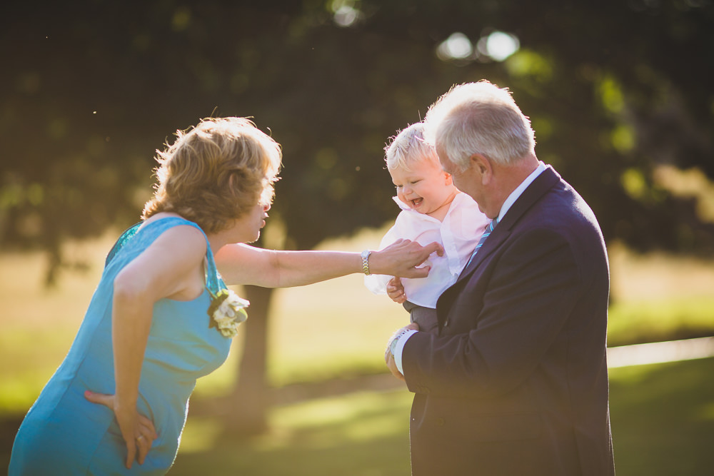 bride and grooms son being tickled