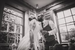 bride and groom kiss during speeaches