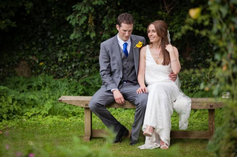 bride and groom on bench in colour