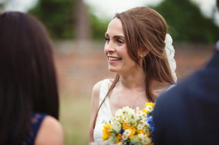 Bride smiling at arriving guests