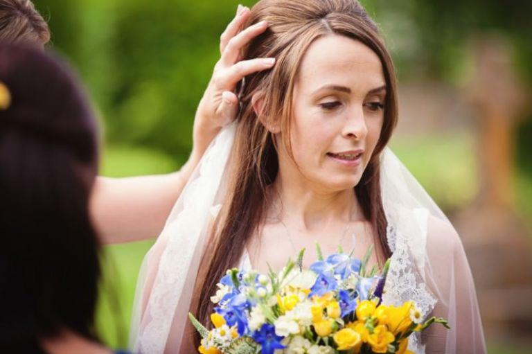 Bridesmaid fixing bride's hair