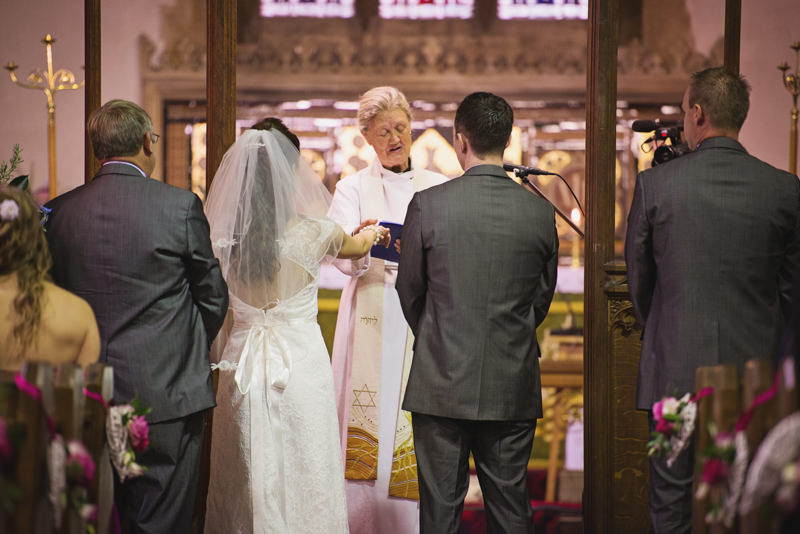 Vicar passes bride's hand to groom