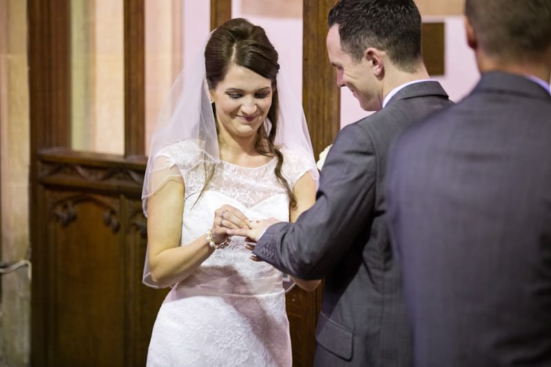Bride puts ring on grooms hand
