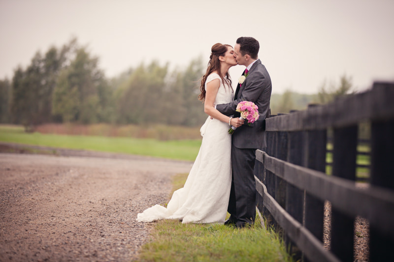 bride and groom lean on fence and kiss