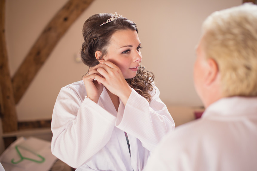 bride putting on ear rings