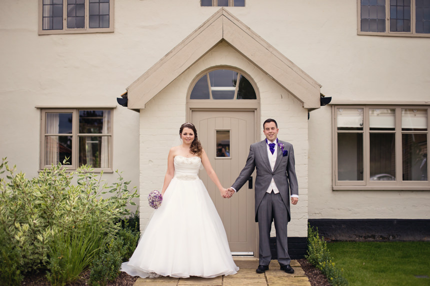 bride and groom in front of house
