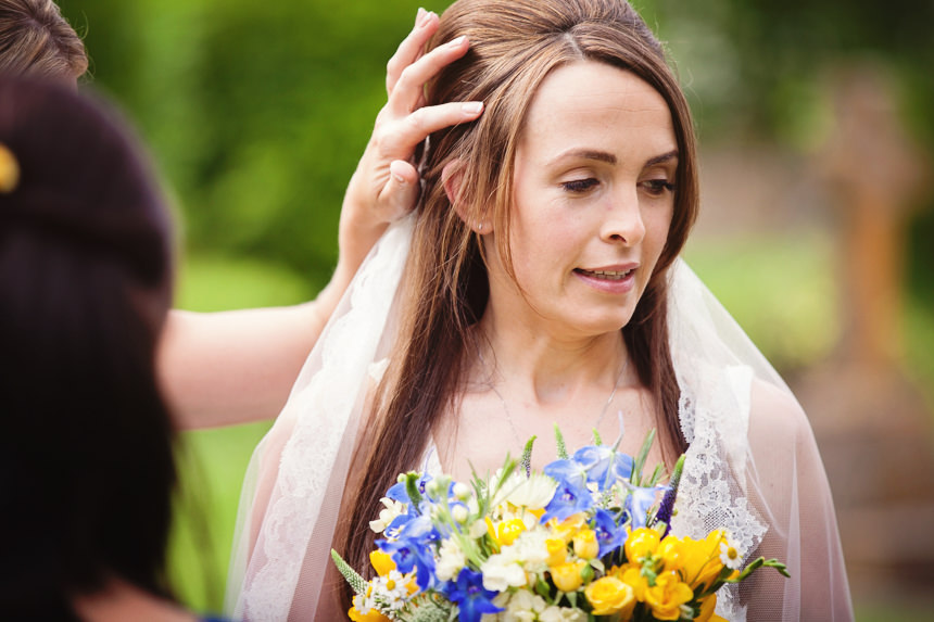 Bridesmaid fixing bride's hair
