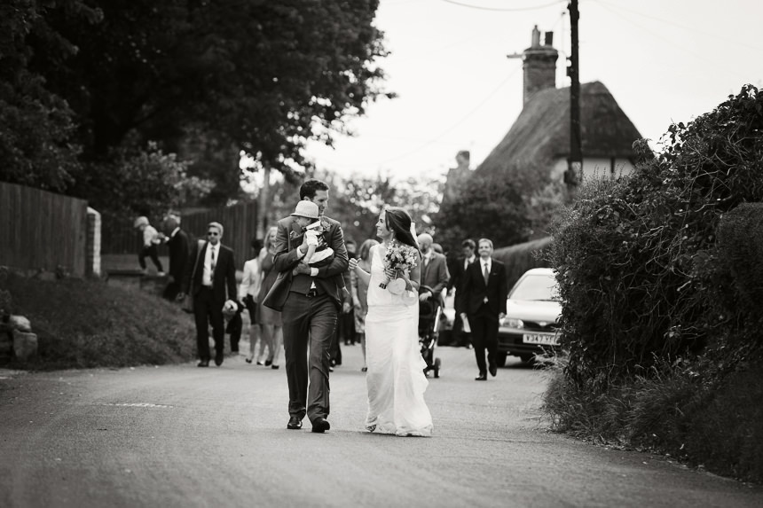 Bride, Groom and their son walking back from the church, black and white