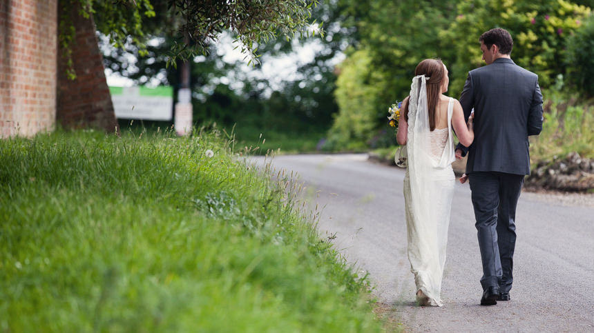 bride and groom walking with son shot from behind