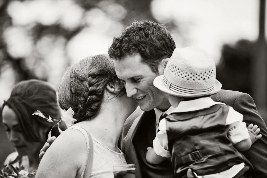 groom holding son greeting guest