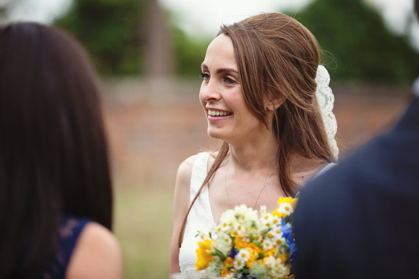 Bride smiling at arriving guests