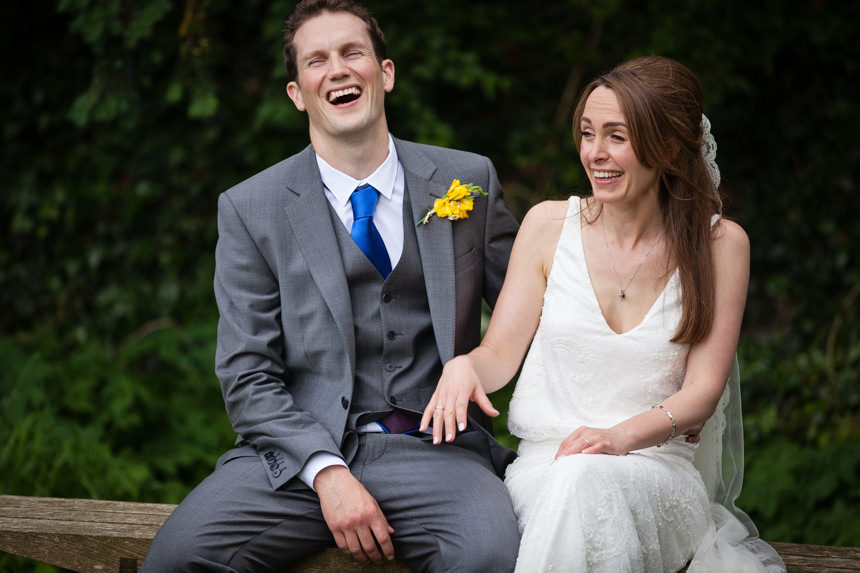 bride and groom on bench laughing