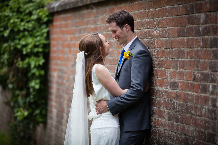 bride and groom hugging against stone wall