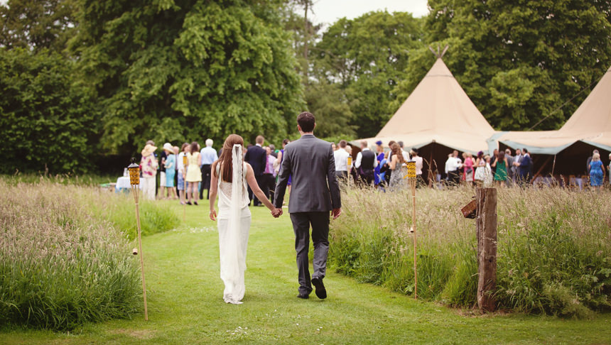 bride and groom walking back to join guests