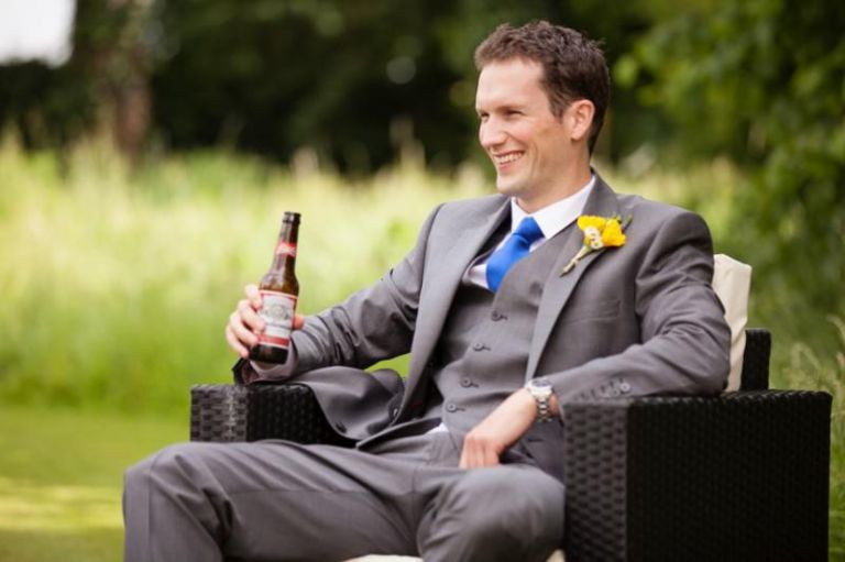 best man laughing with a beer