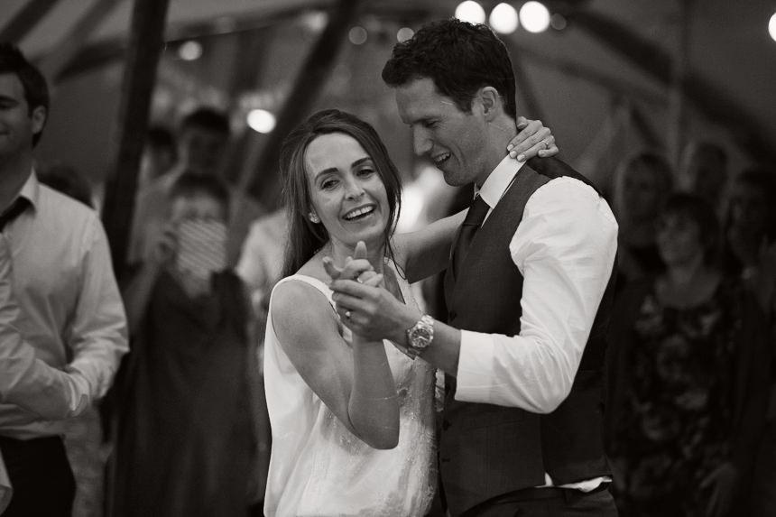 bride and groom looking happy on the dance floor