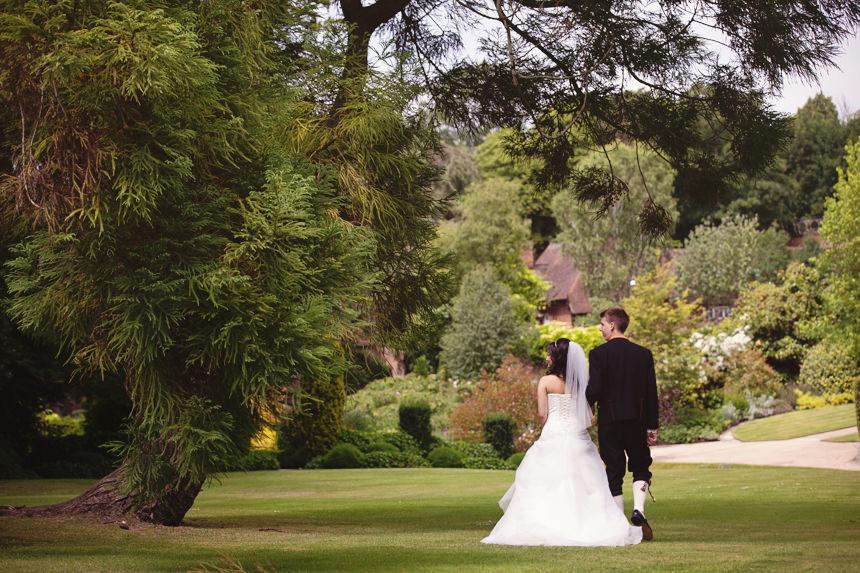 bride and groom walking under tree