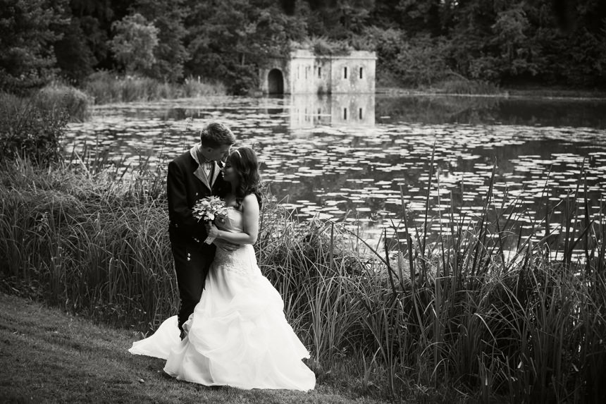 B + W bride and groom by lake