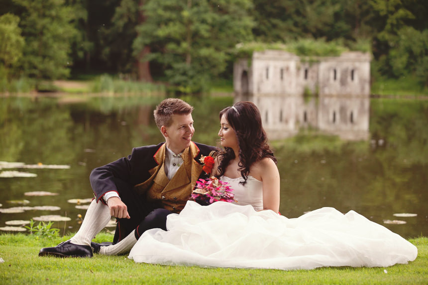 bride and groom sitting by lake