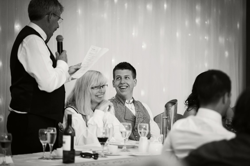 groom laughing at his father's speech