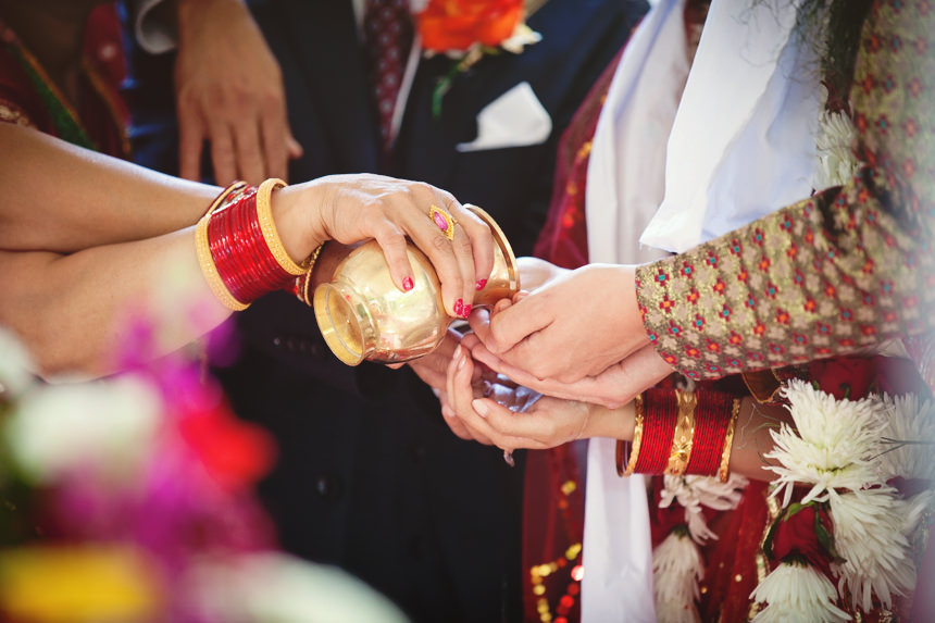 guests pour water into bride and groom's hands