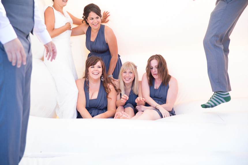 bridesmaids sitting on bouncy castle laughing