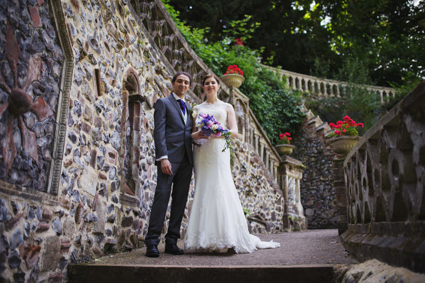 bride and groom next to wall