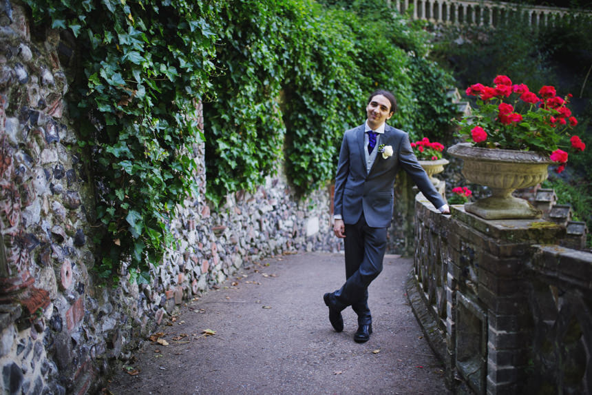 groom leaning on wall