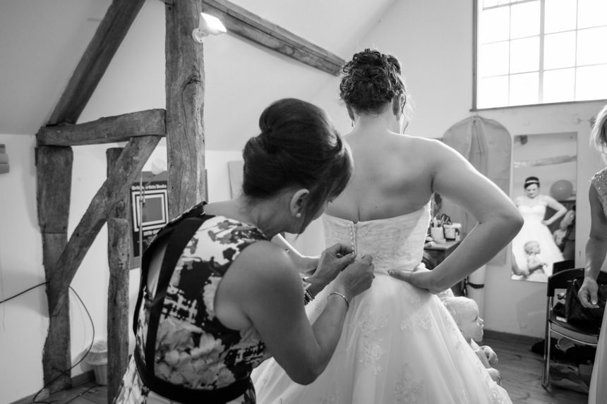 Buttoning up bride's dress