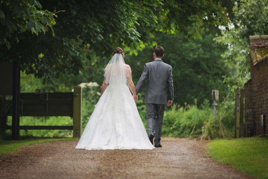Bride and groom walking holding hands