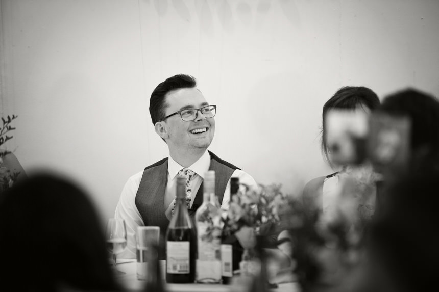 Groom laughing at best man speech