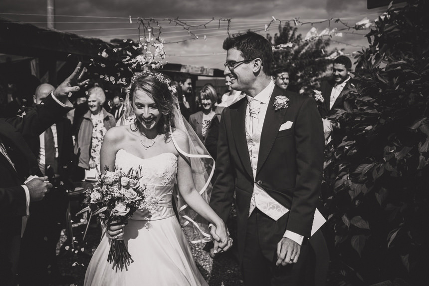 bride and groom walking in confetti