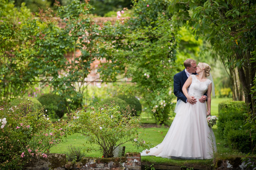 bride and groom kiss in garden
