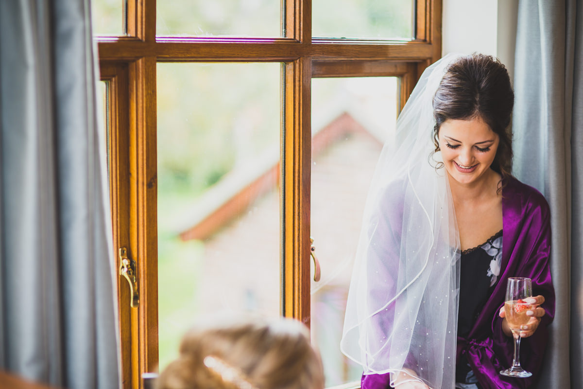 bride sitting by window smiling