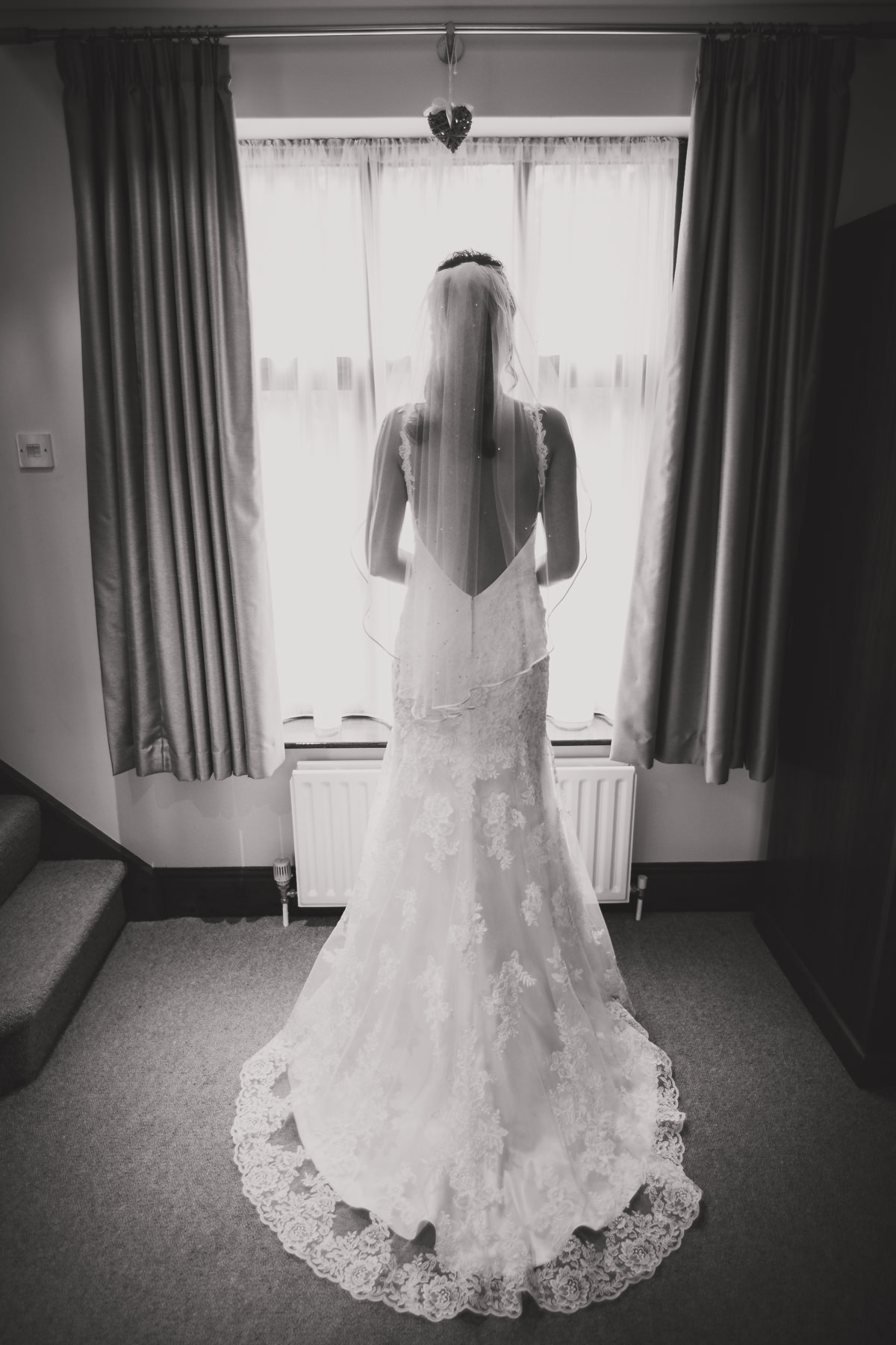 bride in dress standing in front of window