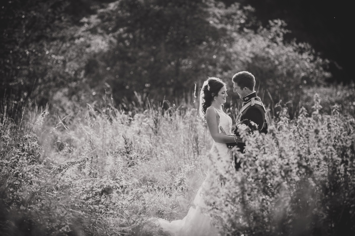 black and white of bride and groom in grass