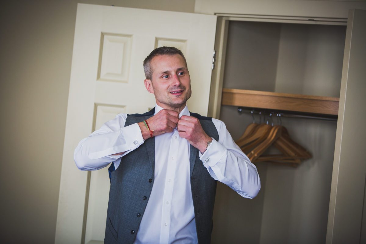 groom doing shirt up