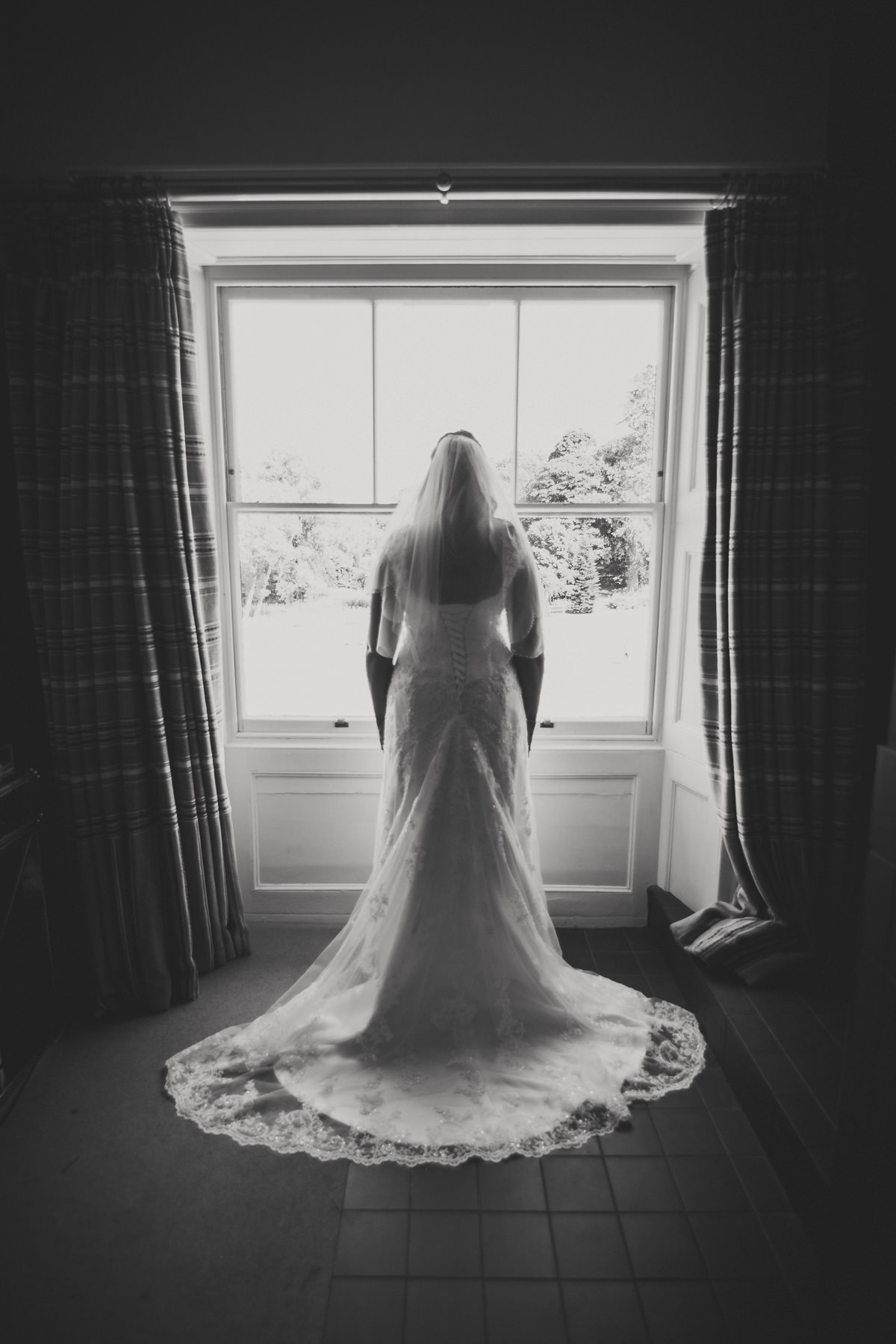bride in dress in window