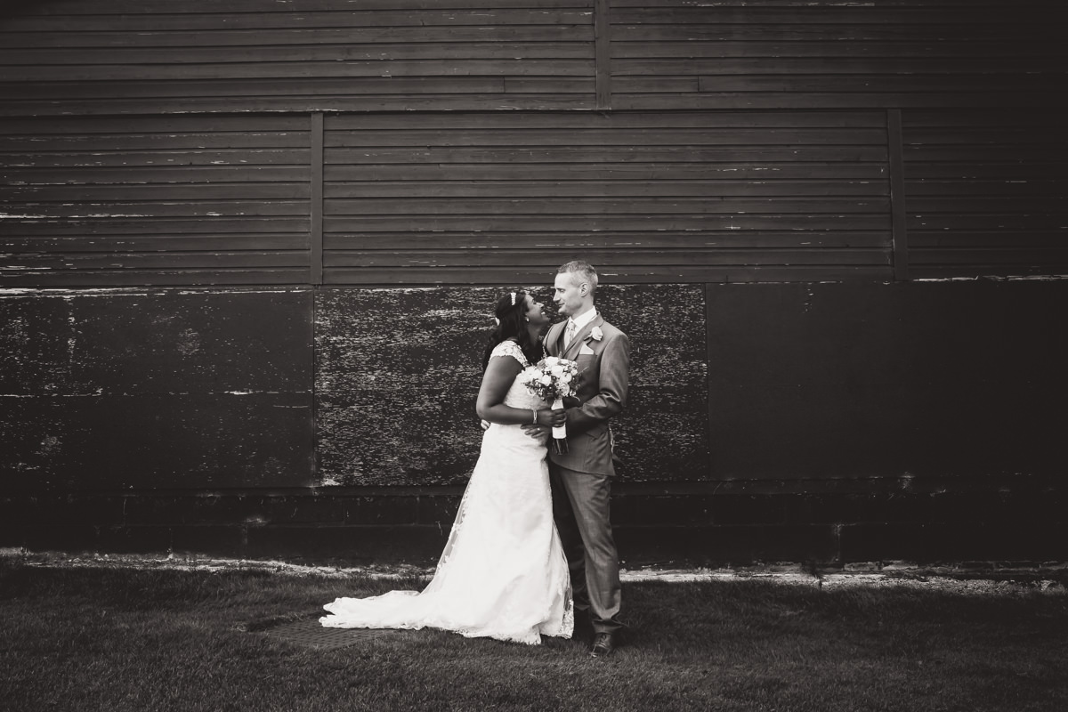 bride and groom in front of barn wall