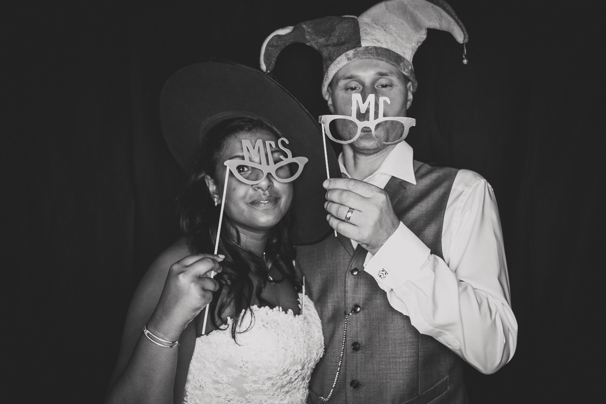 bride and groom holding mr and mrs signs in photo booth