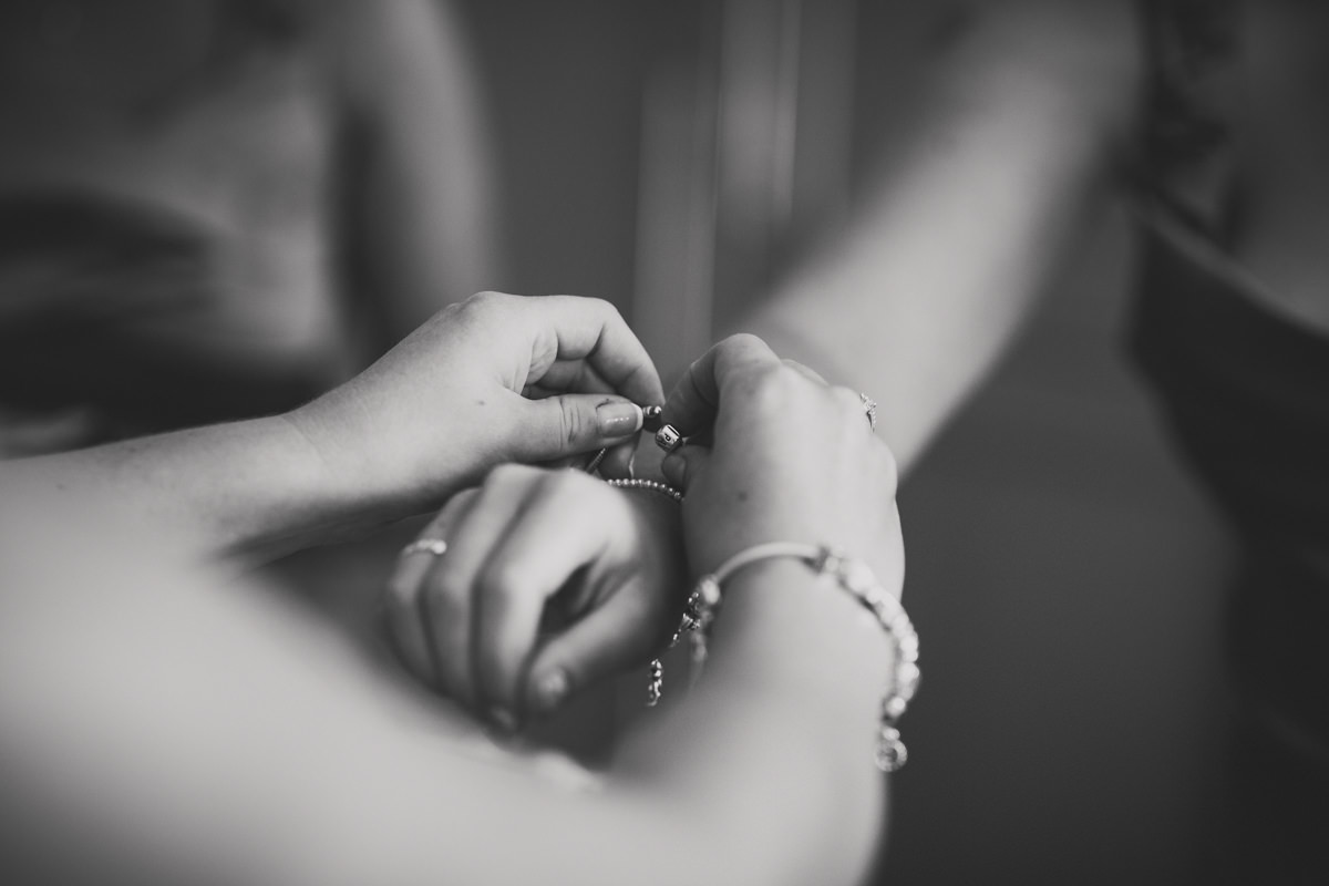 bridesmaid putting on bracelet
