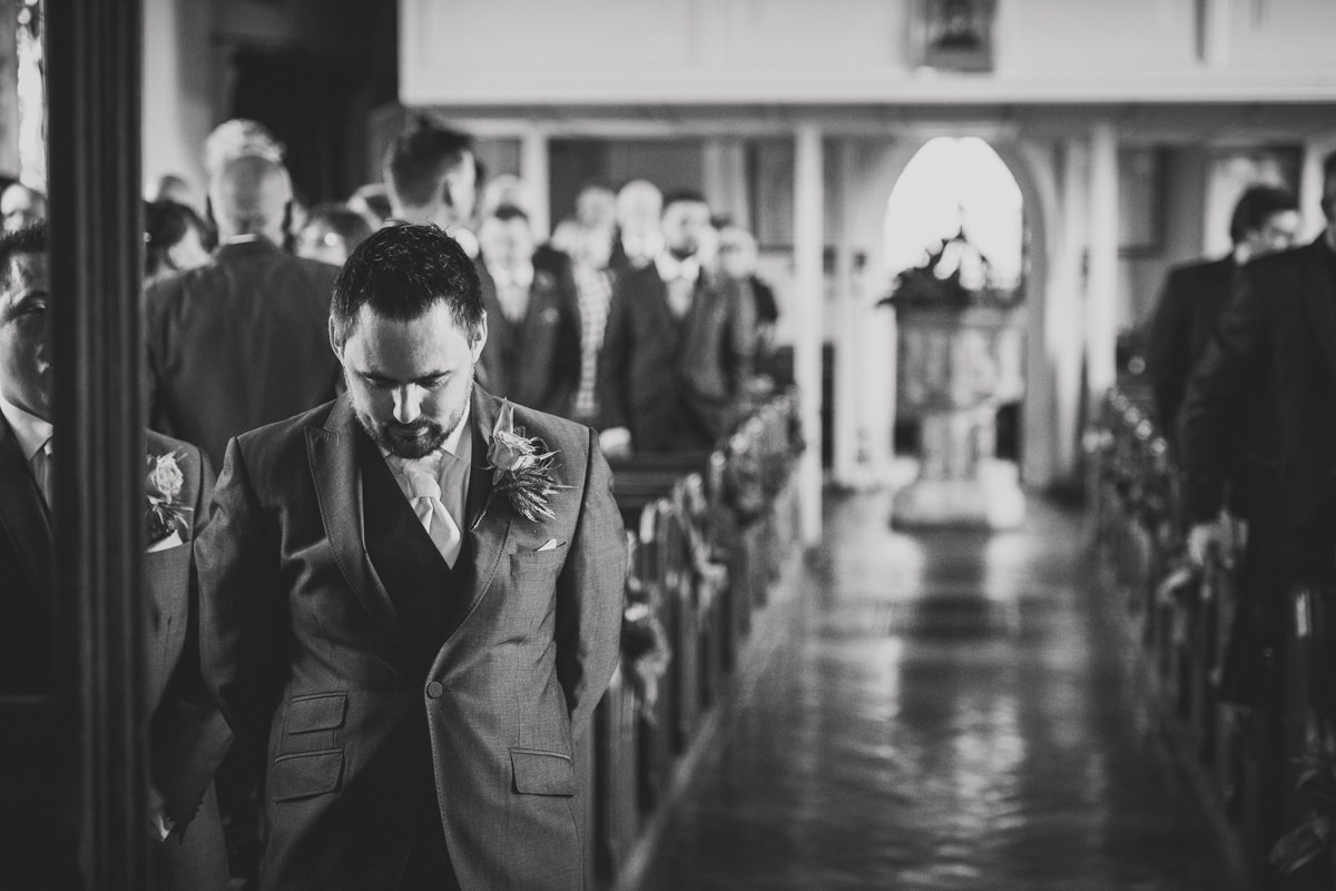 groom waiting at alter