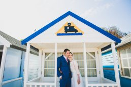 couple standing under beach hut