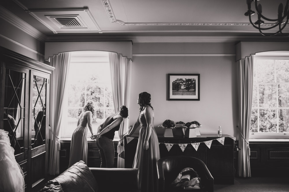 bride and bridesmaids looking out window