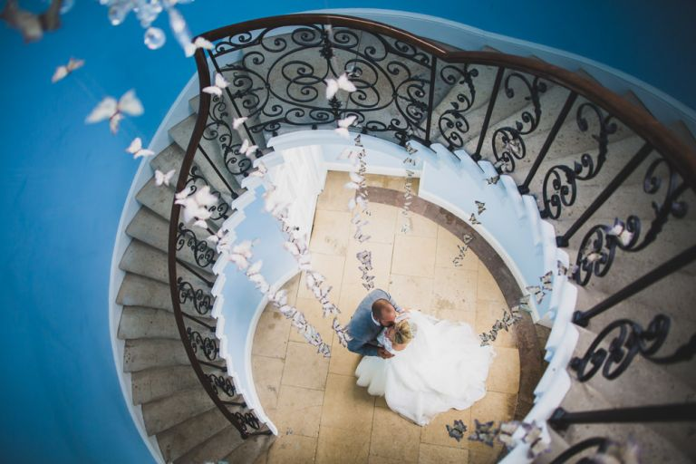 bride and groom under stair case at Kimberly Hall