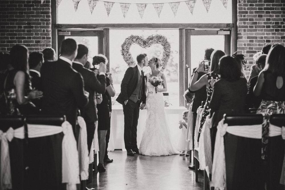 bride and groom kissing at front of ceremony